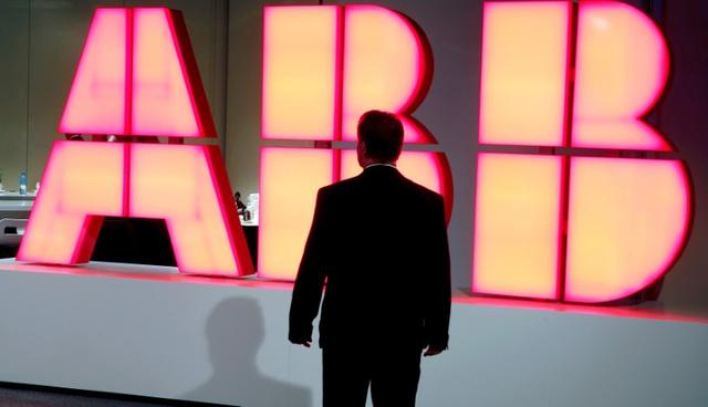 FILE PHOTO: A man stands in front of the logo of Swiss engineering group ABB before a news conference in Zurich, Switzerland October 4, 2016. REUTERS/Arnd Wiegmann/File Photo