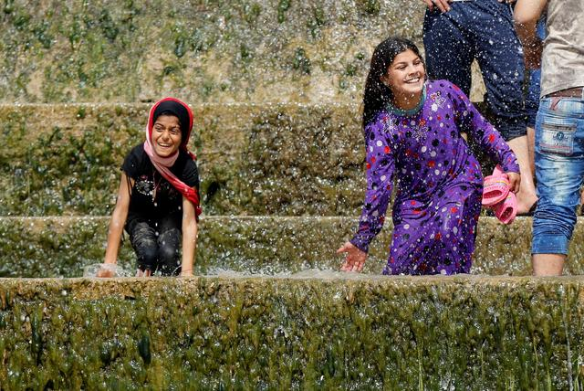 Iraqi girls play with water as they enjoy their Friday holiday with their family at Shallalat district (Arabic for ''waterfalls'') in eastern Mosul, Iraq, April 21, 2017. REUTERS/ Muhammad Hamed