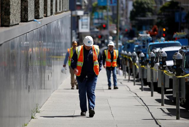 A worker with Pacific Gas and Electric (PG&E) walks on Eddy Street after a fire broke out at a substation in San Francisco, California, U.S., April 21, 2017. REUTERS/Stephen Lam