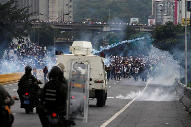FILE PHOTO: Police fire tear gas toward opposition supporters during clashes while rallying against Venezuela's President Nicolas Maduro in Caracas, Venezuela. REUTERS/Carlos Garcia Rawlins