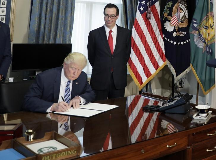 U.S. President Donald Trump (L) signs a financial services executive order as Treasury Secretary Steven Mnuchin (R) looks on at the Treasury Department in Washington, U.S., April 21, 2017. REUTERS/Kevin Lamarque/Files