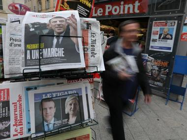 A man walks past a rack which displays copies of French daily newspapers...
