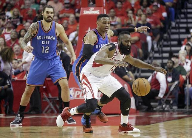 4月25日、米プロバスケットボール協会(NBA)は各地でプレーオフ1回戦(7回戦制)の試合を行い、ロケッツがジェームズ・ハーデン(白13番)による34得点の活躍などでサンダーに105─99で勝利。4勝1敗として1回戦突破を決めた(2017年 ロイター/Thomas B. Shea-USA TODAY Sports)