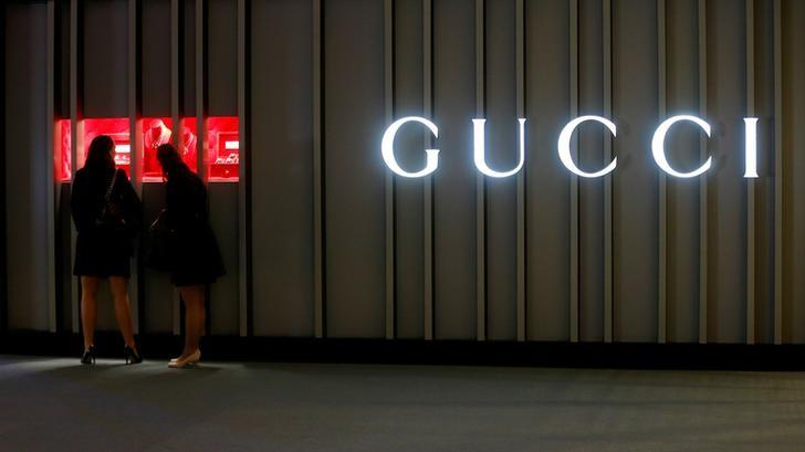 Visitors stand in front of a display window of Gucci at the Baselworld watch and jewellery fair in Basel, Switzerland March 22, 2017. REUTERS/Arnd Wiegmann/Files