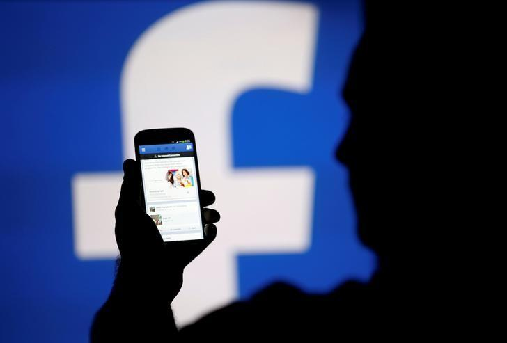 FILE PHOTO: A man is silhouetted against a video screen with a Facebook logo as he poses with a Samsung S4 smartphone in this photo illustration August 14, 2013. REUTERS/Dado Ruvic/File Photo