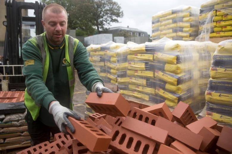 FILE PHOTO - A worker stacks bricks at the Vauxhall depot of building material supplier Travis Perkins in London, Britain, October 25, 2013.   REUTERS/Neil Hall/File Photo
