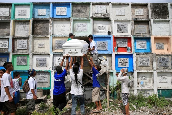 Loved ones and mourners lift up a closed coffin of Arjay Suldao, 16, who according to the local media was a victim of unknown assailants related to the drug war, to place it inside an apartment-type tomb, during his funeral at a cemetery in Navotas city, metro Manila, Philippines March 28, 2017. REUTERS/Romeo Ranoco/Files