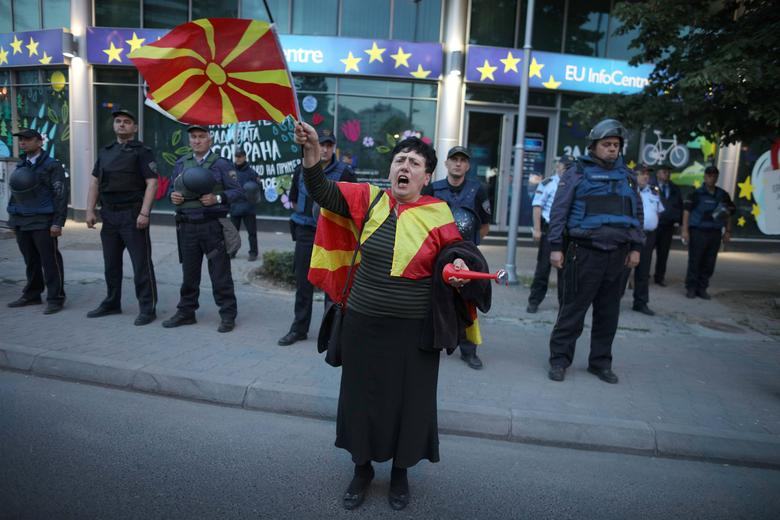 A woman sings Macedonian national anthem during the demonstrations in front of the EU Info Center building in Skopje, Macedonia, April 28, 2017. REUTERS/Stoyan Nenov