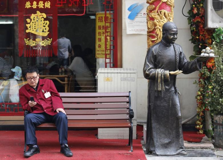 A man sits on a bench in front of a restaurant at a shopping district in Beijing May 6, 2013. REUTERS/Kim Kyung-Hoon