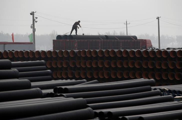 A worker packs pipelines onto a truck at a local plastic pipe factory in Donghegang village on the outskirts of Xiongxian county, one part of the new special economic zone Xiong'an New Area, Hebei province, China, April 6, 2017. REUTERS/Jason Lee/Files