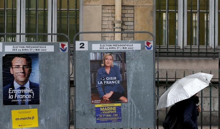 A woman walks past the new official posters for the candidates for the 2017 French presidential election, Emmanuel Macron, head of the political movement En Marche !, or Onwards !, (L) and Marine Le Pen, French National Front (FN) political party leader (R), in Paris, France, April 28, 2017. REUTERS/Gonzalo Fuentes