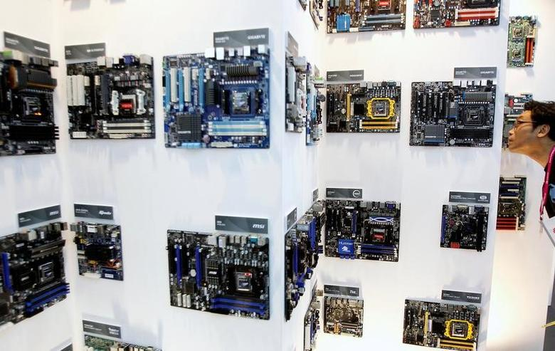 A man looks at motherboards displayed at the AMD booth during the Computex 2011 computer fair at the TWTC Nangang exhibition hall in Taipei May 31, 2011.  REUTERS/Pichi Chuang/File Photo