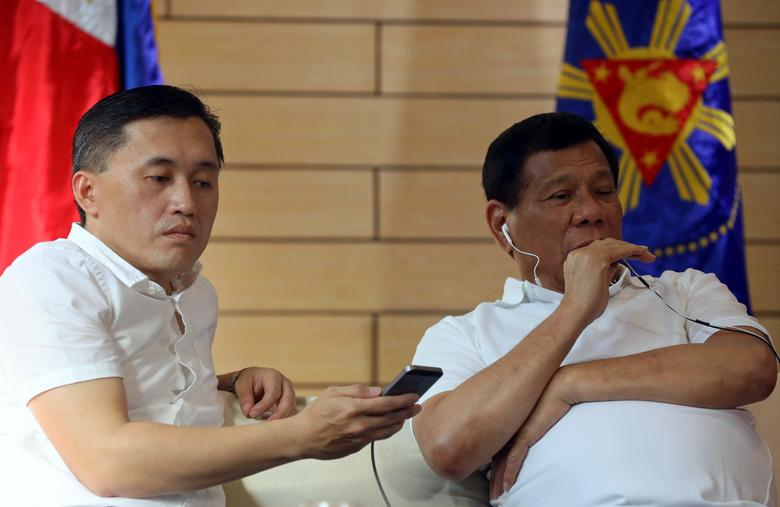 Philippine President Rodrigo Duterte (R) speaks with China's President Xi Jinping over the phone while with Christopher 'Bong' Go, Special Assistant to the President, in Davao City, southern Philippines May 3, 2017. Malacanang Photo/Handout via REUTERS