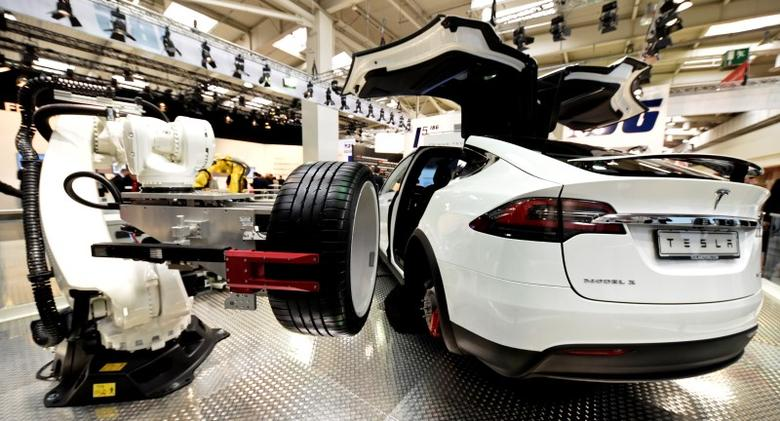 A robotic arm changes the tyre of a Tesla car at the world's biggest industrial fair, ''Hannover Fair'', in Hanover, Germany April 24, 2017. REUTERS/Fabian Bimmer