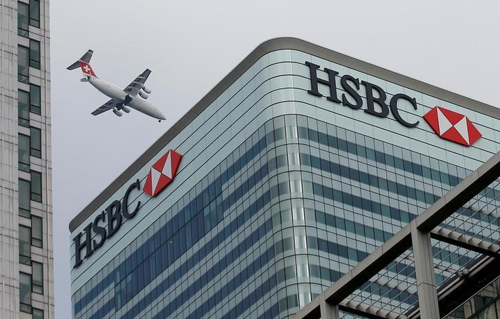 An aircraft flies past the HSBC headquarters building in the Canary Wharf financial district in east London February 15, 2015.   REUTERS/Peter Nicholls/Files