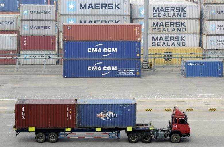 A truck carrying shipping containers travels at a port in Qingdao, Shandong province, China, October 13, 2015.  REUTERS/Stringer