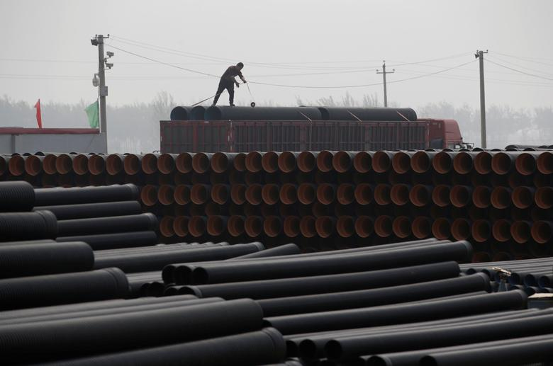 A worker packs pipelines onto a truck at a local plastic pipe factory in Donghegang village on the outskirts of Xiongxian county, one part of the new special economic zone Xiong'an New Area, Hebei province, China, April 6, 2017. REUTERS/Jason Lee