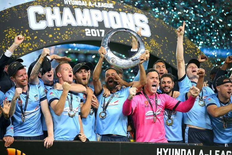 Players and team staff from Sydney FC celebrate with the trophy after defeating Melbourne Victory in the A-League soccer final at the Sydney Football Stadium in Australia, May 7, 2017.       AAP/David Moir/via REUTERS
