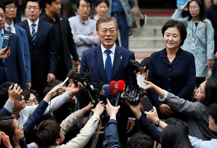 Moon Jae-in, the presidential candidate of the Democratic Party of Korea, and his wife Kim Jung-sook speak to the media after voting at a polling station in Seoul, South Korea, May 9, 2017. REUTERS/Kim Kyung-Hoon