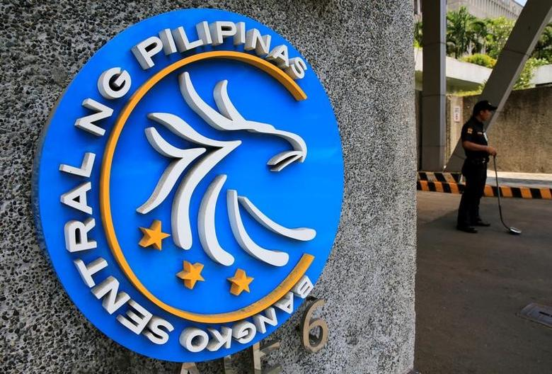 A security guard stands beside a logo of the Bangko Sentral ng Pilipinas (Central Bank of the Philippines) posted at the main gate in Manila, Philippines April 28, 2016.  REUTERS/Romeo Ranoco