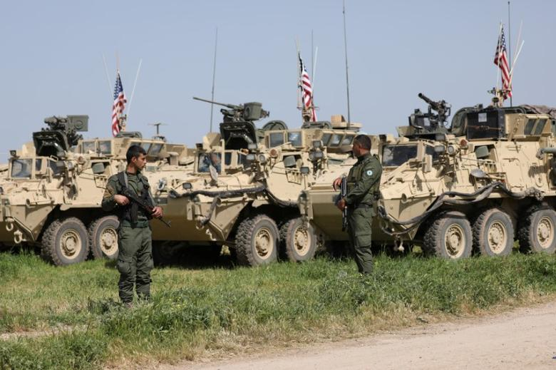 FILE PHOTO: Kurdish fighters from the People's Protection Units (YPG) stand near U.S military vehicles in the town of Darbasiya next to the Turkish border, Syria April 29, 2017. Picture taken April 29, 2017. REUTERS/Rodi Said