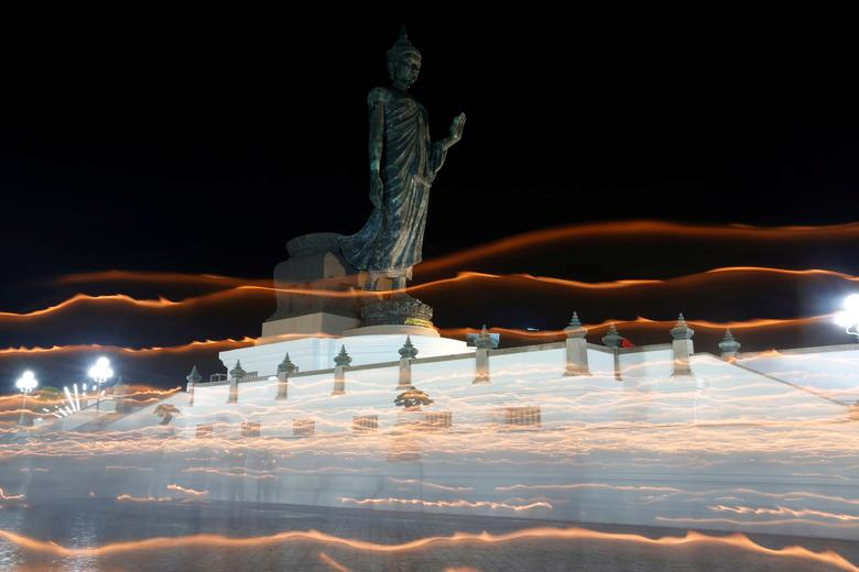 Buddhists carry candles while encircling a large Buddha statue during Vesak Day, an annual celebration of Buddha's birth, enlightenment and death, at a temple in Nakhon Pathom province on the outskirts of Bangkok. Picture taken using long exposure. REUTERS/Chaiwat Subprasom