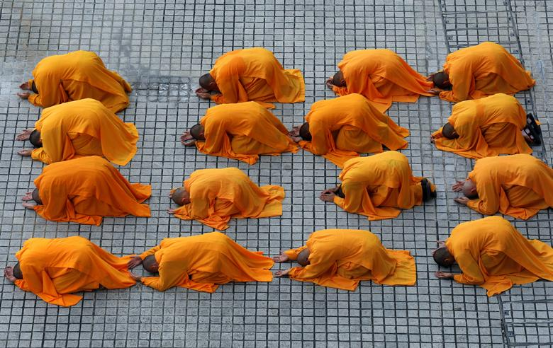 Buddhist monks prostrate as they perform the
