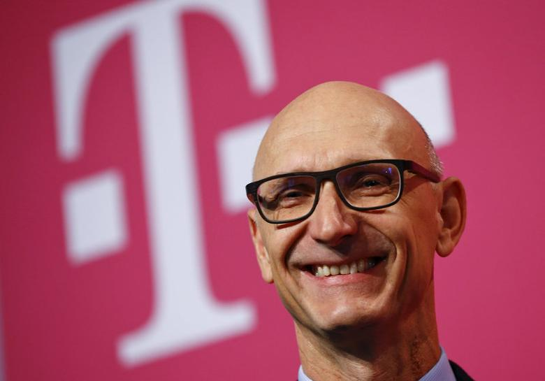 FILE PHOTO: Timotheus Hoettges, CEO of Germany's telecommunications giant Deutsche Telekom AG is all smiles as he poses in front of the company's logo at Telekom's annual news conference in Bonn February 25, 2016. REUTERS/Wolfgang Rattay/File Photo