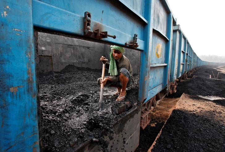 A worker unloads coal from a goods train at a railway yard in the northern city of Chandigarh, India, July 8, 2014. REUTERS/Ajay Verma/File Photo