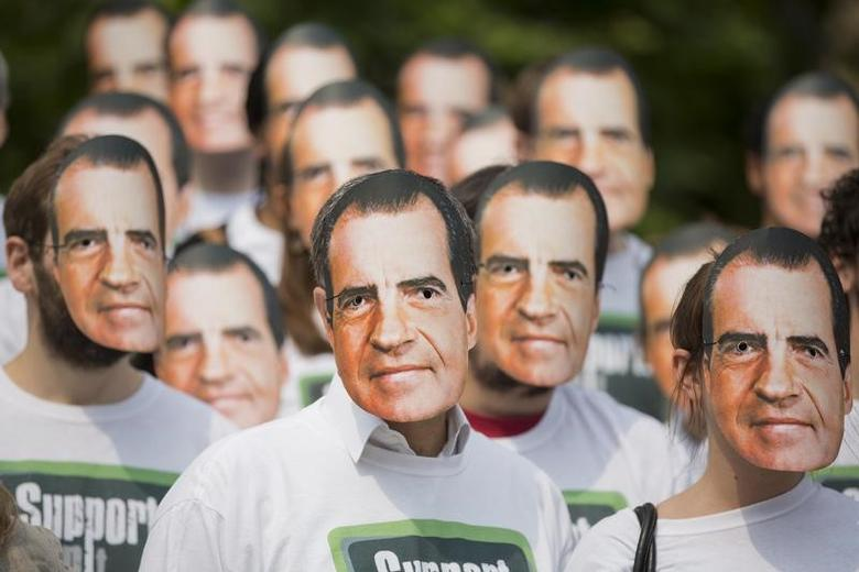 Protesters from the ''Support, Don't Punish'' campaign group wear masks depicting former US President Richard Nixon to demonstrate against the criminalisation of drug use in London June 26, 2013. REUTERS/Neil Hall