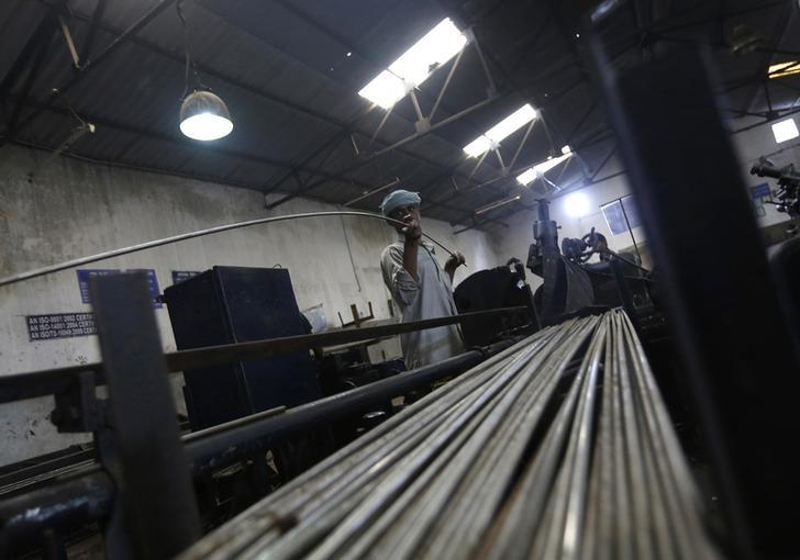 An employee holds a steel rod as he works on the production line inside Hallmark steel factory in Bhiwadi in Rajasthan September 30, 2013.  REUTERS/Adnan Abidi/Files
