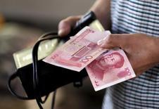 Imagen de una persona con unos billetes de 100 yuanes en billetes en un mercado en Pekín, ago 12, 2015. Los bancos chinos ofrecieron inesperadamente más crédito en abril en comparación con el mes anterior, lo que subraya el desafío que enfrentan los funcionarios al tratar de reducir los riesgos del aumento de la deuda.  REUTERS/Jason Lee