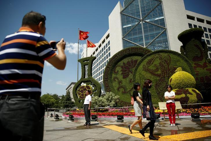 A man takes pictures of a flower display set up ahead of the Belt and Road Forum in central Beijing, China, May 10, 2017.  REUTERS/Thomas Peter