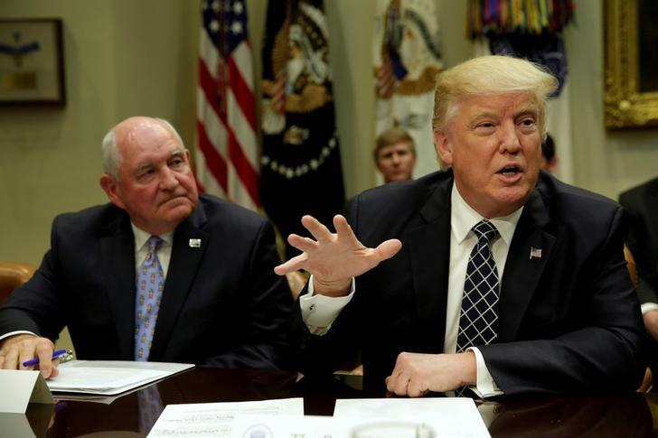 FILE PHOTO - U.S. President Donald Trump talks to the media next to Secretary of Agriculture Sonny Perdue during a roundtable discussion with farmers at the White House in Washington, U.S. on April 25, 2017. REUTERS/Yuri Gripas/File Photo