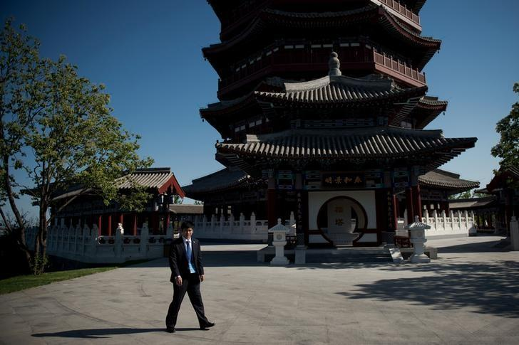 A security official walks past a pagoda at  the Yanqi Lake International Conference Center, where the Belt and Road Forum was being held, north of Beijing, China May 15, 2017.  REUTERS/Nicolas Asfouri/Pool
