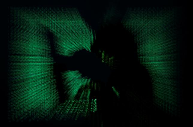 A  hooded man holds laptop computer as cyber code is projected on him in this illustration picture taken on May 13, 2017. REUTERS/Kacper Pempel/Illustration
