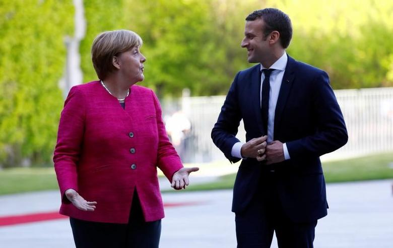 German Chancellor Angela Merkel and French President Emmanuel Macron talk as they arrive at a ceremony at the Chancellery in Berlin, Germany, May 15, 2017.    REUTERS/Pawel Kopczynski