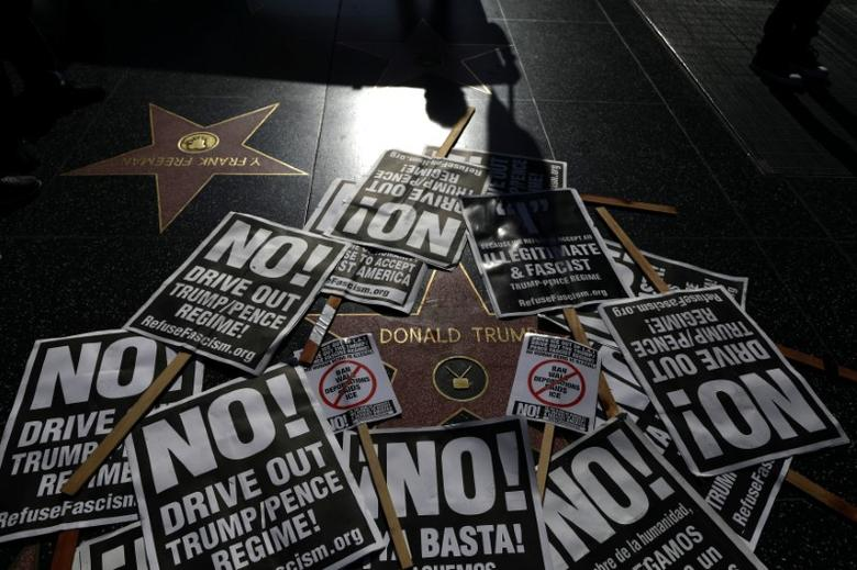 FILE PHOTO: People protest against President Donald Trump's firing of FBI Director James Comey, on Trump's star on the Hollywood Walk of Fame in Los Angeles, California, U.S. May 12, 2017. REUTERS/Lucy Nicholson