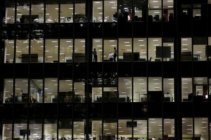 Workers are seen in office windows in the financial district of Canary Wharf in London, Britain, November 3, 2015.    REUTERS/Kevin Coombs/File Photo