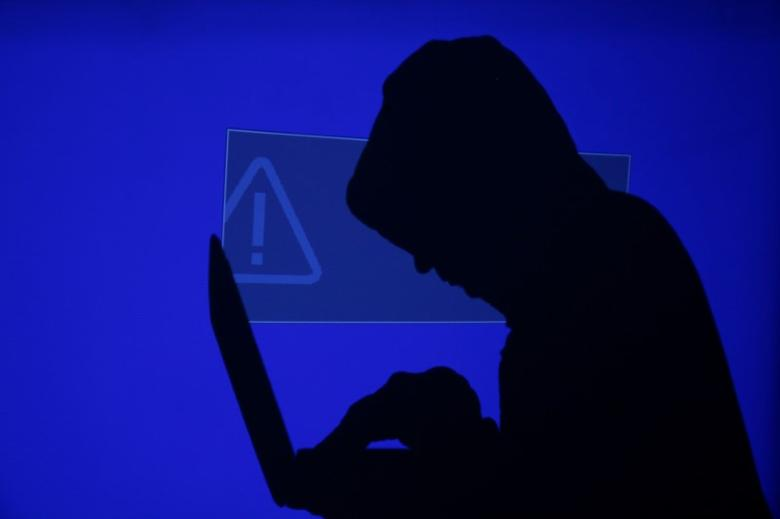 A hooded man holds a laptop computer as blue screen with an exclamation mark is projected on him in this illustration picture taken on May 13, 2017. REUTERS/Kacper Pempel/Illustration