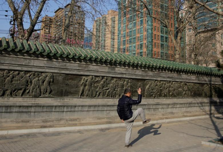 FILE PHOTO: A resident practices Taiji, a traditional form of Chinese martial arts, near apartment blocks in central Beijing, China February 17, 2017. REUTERS/Jason Lee/File Photo