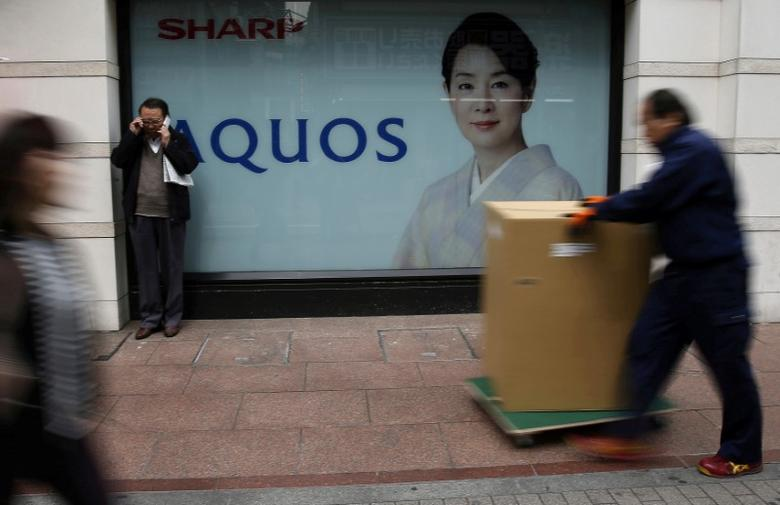 FILE PHOTO: People walk past an advertisement for Sharp Corp's Aquos television outside an electronics