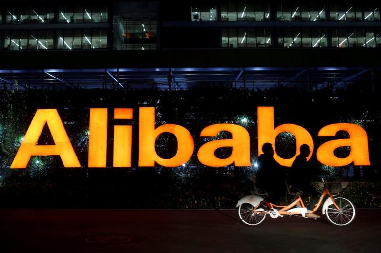FILE PHOTO: People ride a double bicycle past a logo of The Alibaba Group at the company's headquarters on the outskirts of Hangzhou, Zhejiang province November 10, 2014.  REUTERS/Aly Song/File Photo
