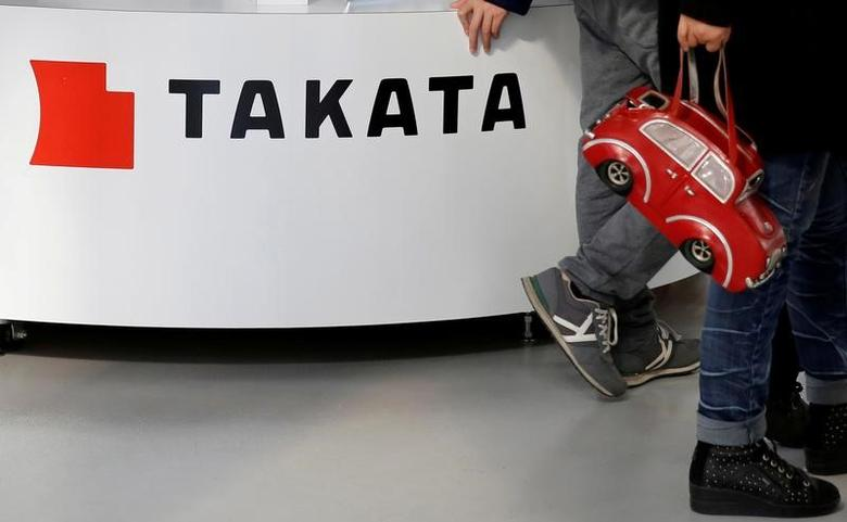 Visitors walk past a logo of Takata Corp on its display at a showroom for vehicles in Tokyo, Japan February 5, 2016. REUTERS/Toru Hanai/Files