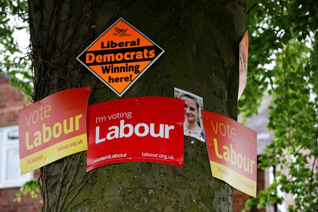 Labour and Liberal Democrat election posters are stuck on a tree alongside a photograph of murdered MP Jo Cox in Lymm, Britain, May 19, 2017. REUTERS/Phil Noble