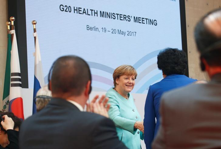 German Chancellor Angela Merkel shakes hands at the meeting of the G20 health ministers in Berlin, Germany, May 19, 2017.   REUTERS/Fabrizio Bensch