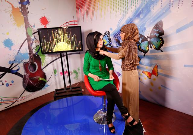Khatira Ahmadi (R), 20, producer of Zan TV station (women's TV), adjusts the headscarf of a presenter before recording in Kabul, Afghanistan May 8, 2017.  REUTERS/Mohammad Ismail
