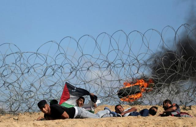 Palestinian protesters take cover during clashes with Israeli troops following a protest against the blockade on Gaza, near the border between Israel and Central Gaza Strip May 19, 2017. REUTERS/Ibraheem Abu Mustafa