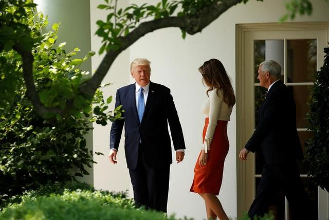U.S. President Donald Trump looks back toward his wife Melania and Vice President Mike Pence as he departs the White House to embark on a trip to the Middle East and Europe, in Washington, U.S., May 19, 2017. REUTERS/Kevin Lamarque