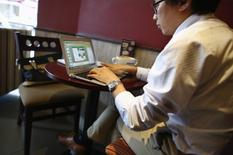 FILE PHOTO: A man works on his computer inside a coffee shop in downtown Shanghai September 25, 2013.  REUTERS/Carlos Barria